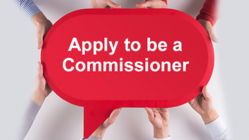 "Hands holding sign that reads: ""Apply to be a Commissioner"""